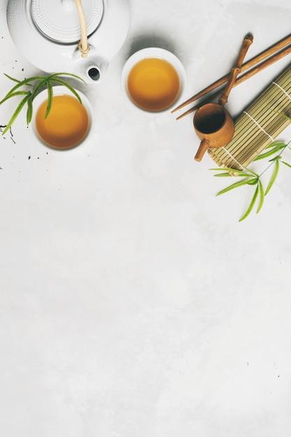 Concept de thé asiatique, deux tasses blanches de thé, théière, service à thé, baguettes, tapis de bambou entourés de thé vert sec sur fond blanc avec espace de copie. infuser et boire du thé. Photo Premium