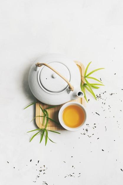 Concept de thé asiatique avec service à thé sur une natte de bambou entourée de thé vert sec Photo Premium