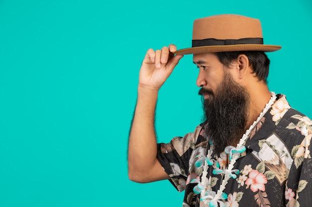 Concept de touristes de sexe masculin qui ont une longue barbe coiffé d'un chapeau sur un bleu. Photo gratuit