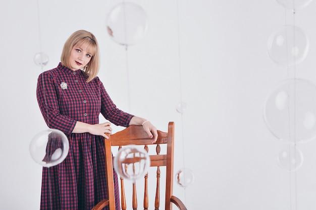 Concept de travail, business model - portrait élégant à la mode d'une femme aux cheveux courts blanc. modèle en robe violette avec broche assis sur une chaise sur fond blanc Photo Premium
