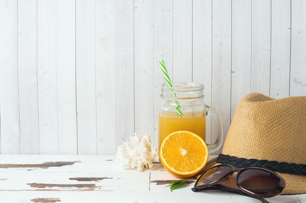 Concept de vacances d'été. chapeau de paille avec jus d'orange et coquillages. espace de copie. Photo Premium