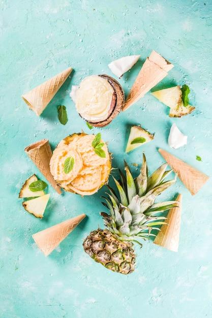 Concept de vacances d'été, définissez divers sorbets de crème glacée tropicale, jus congelés à l'ananas, au pamplemousse et à la noix de coco, béton bleu clair Photo Premium
