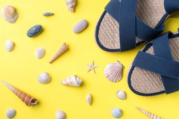 Le concept de vacances d'été. sandales d'été des femmes coquillages sur fond jaune Photo Premium