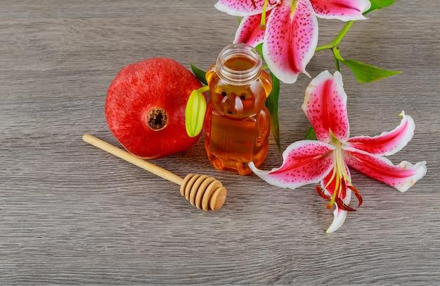 Concept de vacances juives de rosh hashanah - nourriture juive à la grenade, au miel, aux lys roses, symbole Photo Premium
