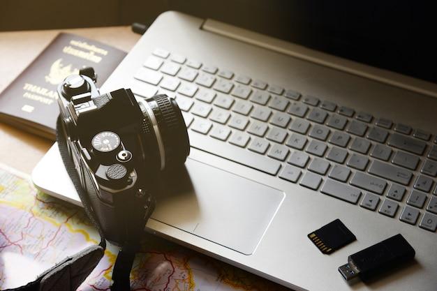 Concept de vacances passeport caméra lecteur flash stockage carte ordinateur portable sur fond de bureau en bois Photo Premium