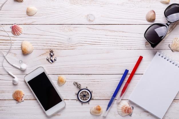 Concept de vacances voyage avec des écouteurs, lunettes de soleil, smartphone, coquillages, ordinateur portable. vue de dessus avec espace de copie. pose à plat Photo Premium