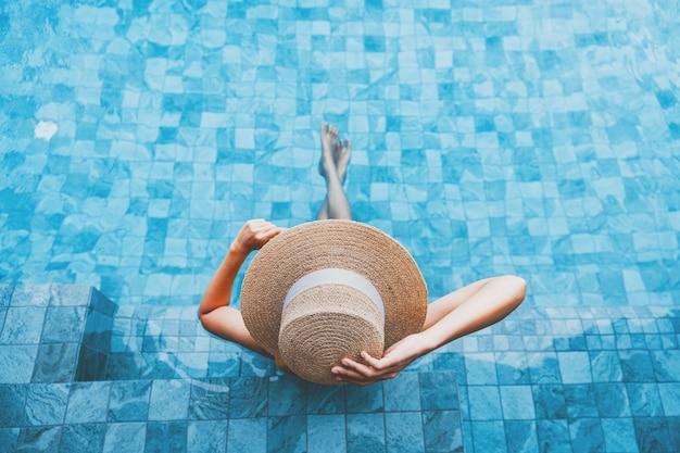 Concept De Vacances De Voyage D'été, Femme Asiatique De Voyageur Heureux Avec Chapeau Et Bikini Se Détendre Dans Un Hôtel De Luxe Avec Piscine à Débordement à La Journée à Phuket, Thaïlande Photo Premium