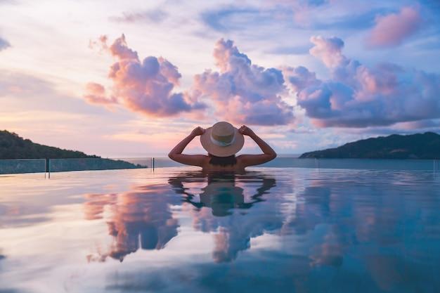 Concept De Vacances De Voyage D'été, Femme Asiatique De Voyageur Heureux Avec Chapeau Et Bikini Se Détendre Dans Un Hôtel De Luxe Avec Piscine à Débordement Avec Plage De La Mer Au Coucher Du Soleil à Phuket, Thaïlande Photo Premium