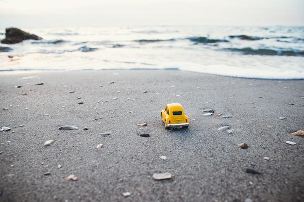 Concept de vacances et de voyage. voiture jouet jaune sur la plage au soleil en été Photo Premium