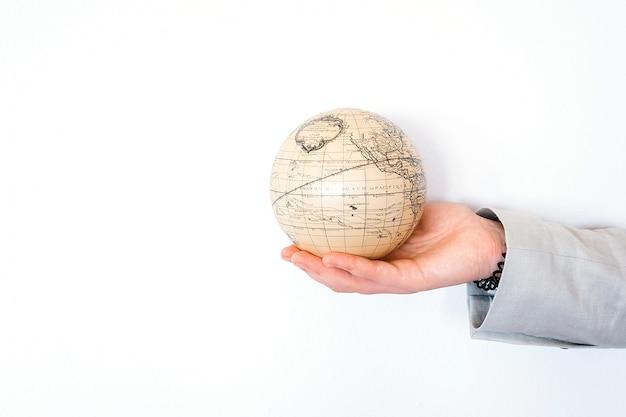 Concept de voyage aventure voyage week-end d'été week-end. vintage globe antique en main isolé sur fond blanc. espace de copie. maquette pour agence de tourisme. idée éducation et découverte Photo Premium