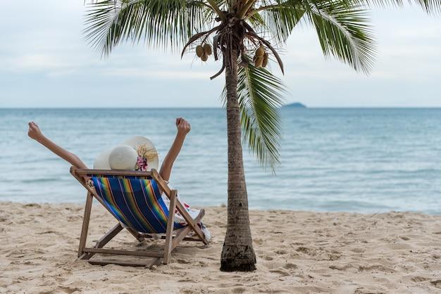 Concept de voyage été plage vacances vacances, heureuse jeune femme asiatique avec chapeau de détente sur la chaise de plage et leva les mains vers le haut. Photo Premium