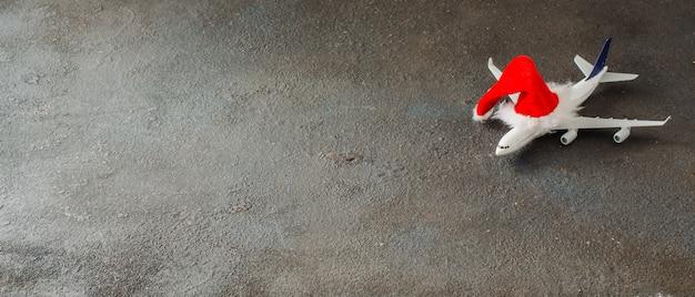 Concept de voyage de noël ou du nouvel an. avion jouet et chapeau de père noël. baner itinérant de noël. Photo Premium