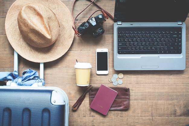Concept de voyage. ordinateur portable sur la table avec les objets du voyageur et son smartphone Photo Premium