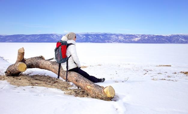 Concept de voyage. randonneuse avec sac à dos enjoing vue sur le lac baïkal, en sibérie, en russie. tourisme d'hiver. Photo Premium