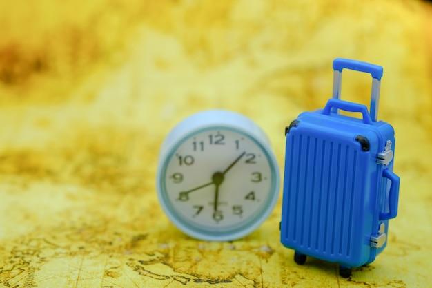 Concept De Voyage Et De Temps. Gros Bagage Bleu Mini Jouet Avec Horloge Ronde Sur La Carte Du Monde. Photo Premium