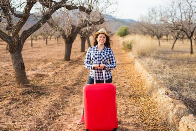 Concept De Voyage, De Tourisme Et De Personnes - Heureuse Jeune Femme Va Voyager Avec Valise Rouge Et Photo Premium