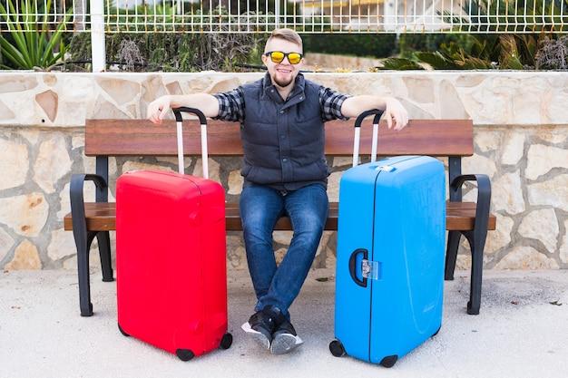 Concept De Voyage, De Tourisme Et De Personnes - Homme Heureux Assis Sur Un Banc Avec Deux Valises, Il Est Prêt à Voyager. Photo Premium