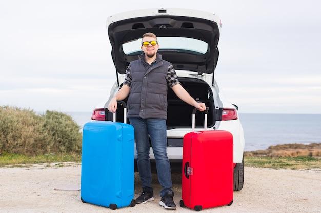 Concept De Voyage, Tourisme Et Voyage - Jeune Homme Assis Dans Le Coffre De La Voiture Ouverte Avec Deux Valises Et Souriant. Photo Premium