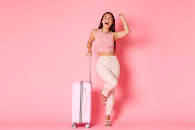 Concept De Voyage, Vacances Et Vacances. Touriste Asiatique Réussie Insouciante Est Arrivée à L'aéroport Avec Une Valise Photo gratuit