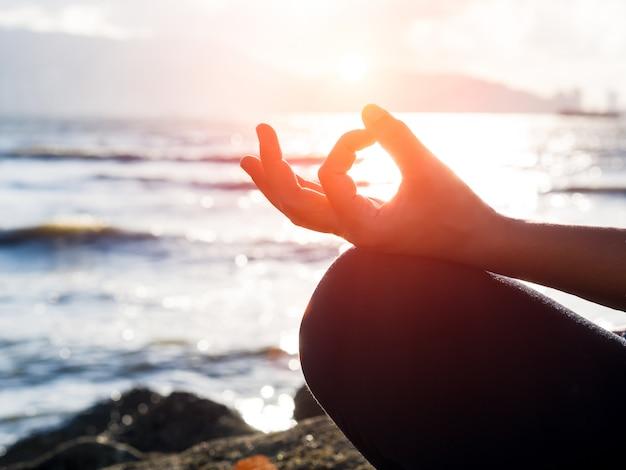 Concept de yoga. closeup main de femme pratiquant la pose de lotus sur la plage au coucher du soleil. Photo Premium