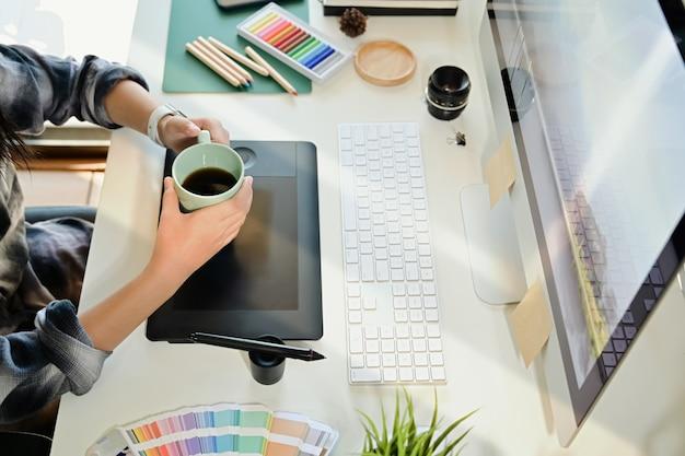 Concepteur créatif tenant une tasse de café sur le lieu de travail studio Photo Premium