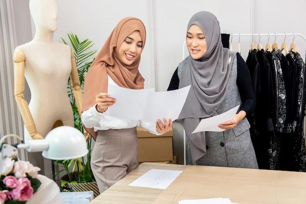 Concepteur de fasion de femme musulmane asiatique travaillant avec un collègue Photo Premium