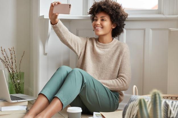 Un Concepteur Noir Joyeux Trouve Une Solution Pour Réaliser Un Projet Brillant, Prend Une Pause-café, Passe Un Appel Vidéo Avec Un Téléphone Portable Photo gratuit