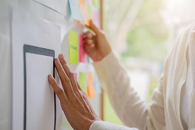 Concepteur de sites web faisant un brainstorming pour un plan stratégique. pense-bête coloré avec des choses à faire à bord du bureau. expérience utilisateur (ux) Photo Premium