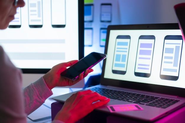 Les Concepteurs D'interfaces Web Développent Une Application Pour Smartphones. L'équipe De Créateurs Travaille Sur Une Interface Avec Les Téléphones Portables. Photo Premium