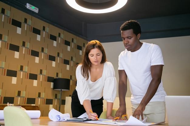 Les Concepteurs Professionnels Prennent Des Notes Sur Le Projet Et Debout Près De La Table Dans L'espace De Coworking Photo gratuit