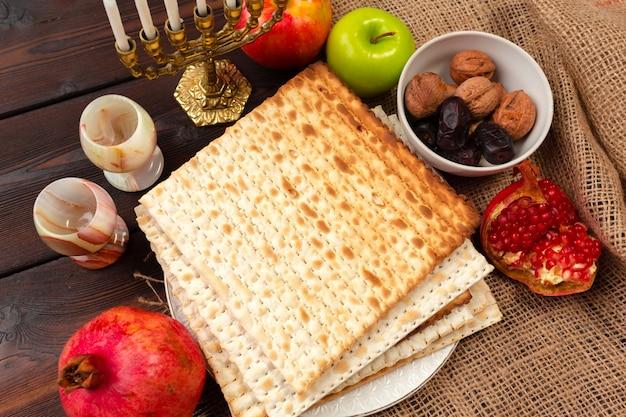 Conception de bannière pâque fête juive avec vin, pain azyme sur fond en bois. Photo Premium