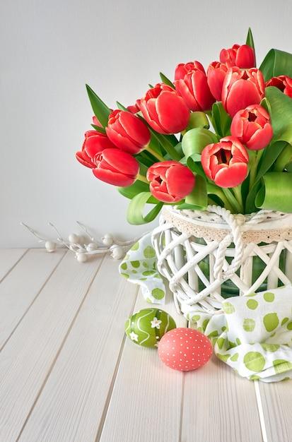 Conception de carte de voeux de pâques avec bouquet de tulipes rouges sur la lumière Photo Premium