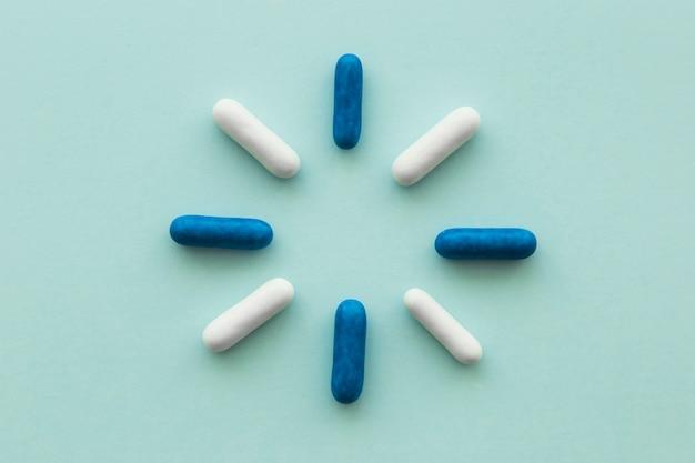 Conception faite avec des capsules bleues et blanches sur fond blanc Photo gratuit