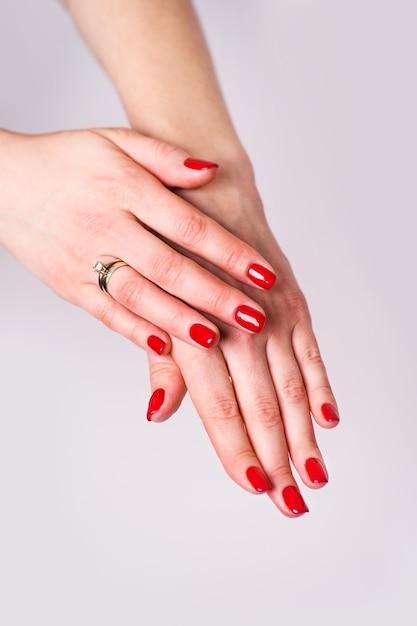 Conception D'ongles. Mains Avec Manucure De Printemps Rouge Vif Sur Fond Gris. Gros Plan Des Mains Féminines. Art Nail. Photo Premium