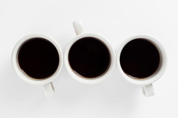 Conception vue de dessus blanche de tasses avec café Photo gratuit