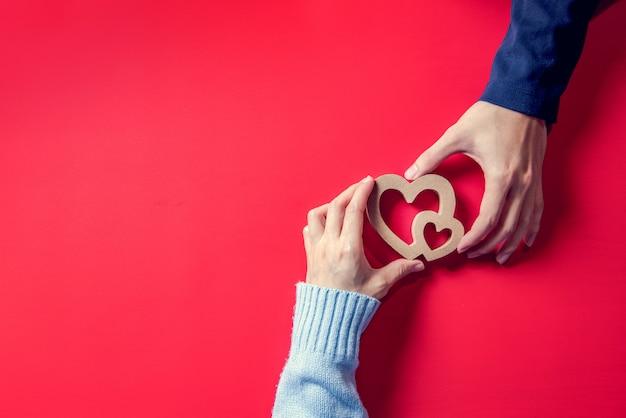 Concepts D'amour, Couple Amoureux De Coeur Sur Les Mains Sur Le Rouge Photo Premium