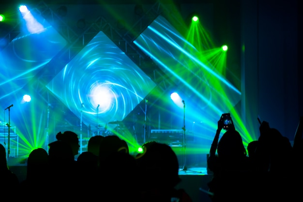 Concert de divertissement défocalisé éclairant sur scène avec la silhouette de personnes Photo Premium