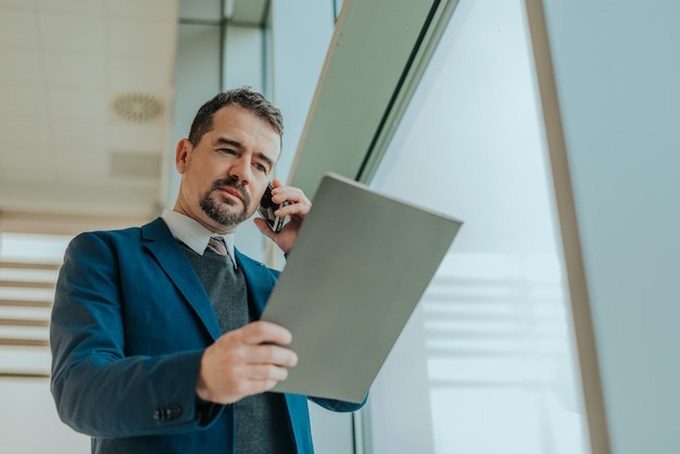 Concessionnaire automobile au téléphone parlant avec le client et regardant les documents de la voiture. Photo Premium