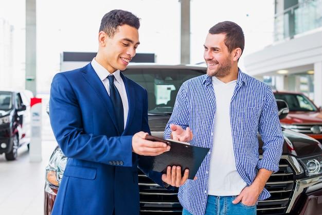Concessionnaire automobile parlant au client Photo gratuit