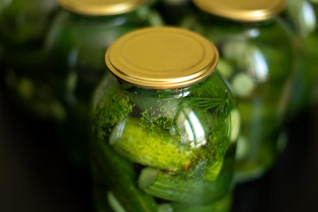 Des concombres en conserve faits à la main dans de grands et petits pots en verre se tiennent sur la table de la cuisine sur un fond de mur gris Photo Premium