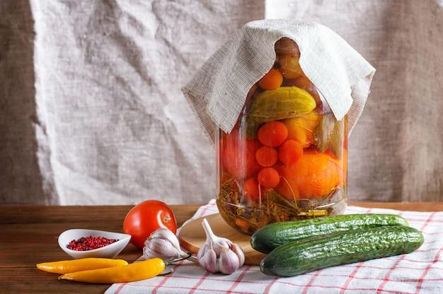 Concombres marinés et tomates dans un bocal en verre sur une nappe en lin et une table en bois. Photo Premium