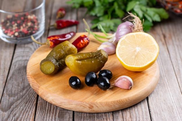 Concombres, Olives, Ail Sur Une Planche De Bois. Cornichons Pour Cuisiner Des Plats Salés Photo Premium