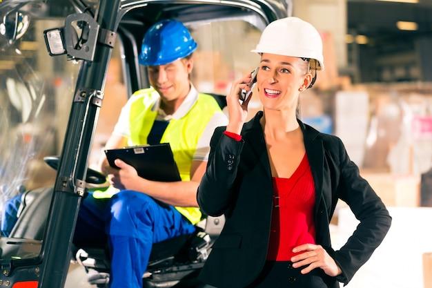 Conducteur de chariot élévateur avec presse-papiers à l'entrepôt d'une entreprise de transport, super visière ou répartiteur avec téléphone Photo Premium