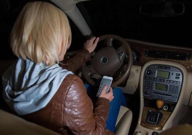 Une conductrice négligente vérifiant son téléphone en conduisant. Photo Premium