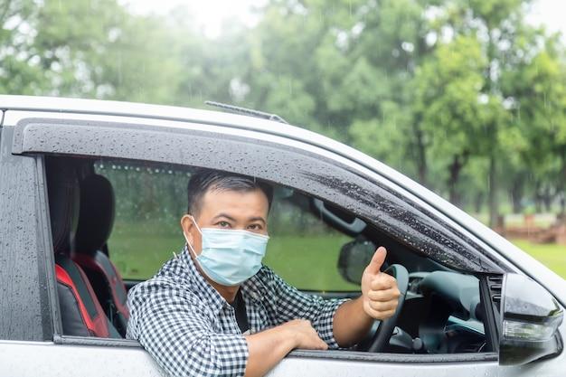 Conduire En Toute Sécurité Par Jour De Pluie. Les Asiatiques Portant Un Masque Sont Assis Dans La Voiture Et Les Pouces Vers Le Haut. Effet De Lumière Parasite Photo Premium