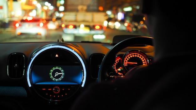 Conduite sur la route la nuit dans la voiture sur le panneau de commande Photo Premium