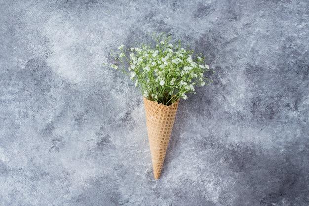 Cône de gaufre avec des fleurs de gypsophile Photo Premium