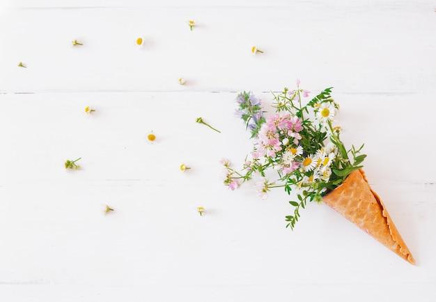 Cône de gaufre avec une fleurs sauvages sur blanc Photo Premium