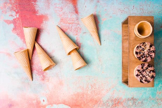 Cônes de gaufres vides et crème glacée au chocolat dans des tasses sur fond multicolore Photo gratuit