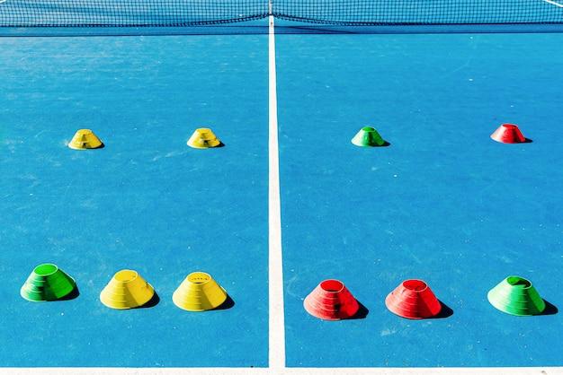 Cônes en plastique colorés sur un court de tennis en ciment bleu avec des lignes blanches Photo Premium